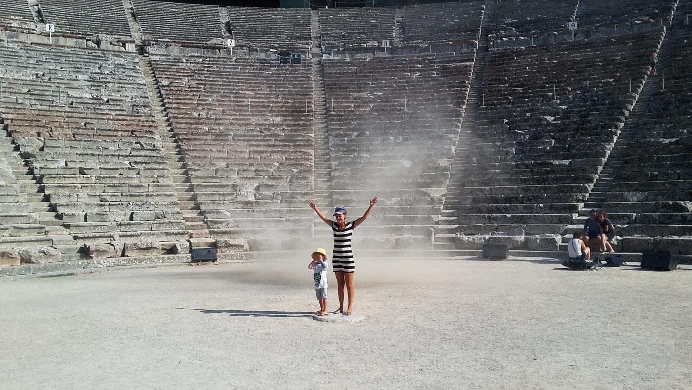 Lea und Luk stehen genau im Zentrum des Amphitheaters in Epidauros. Hinter ihnen zieht eine kleine Windhose vorbei