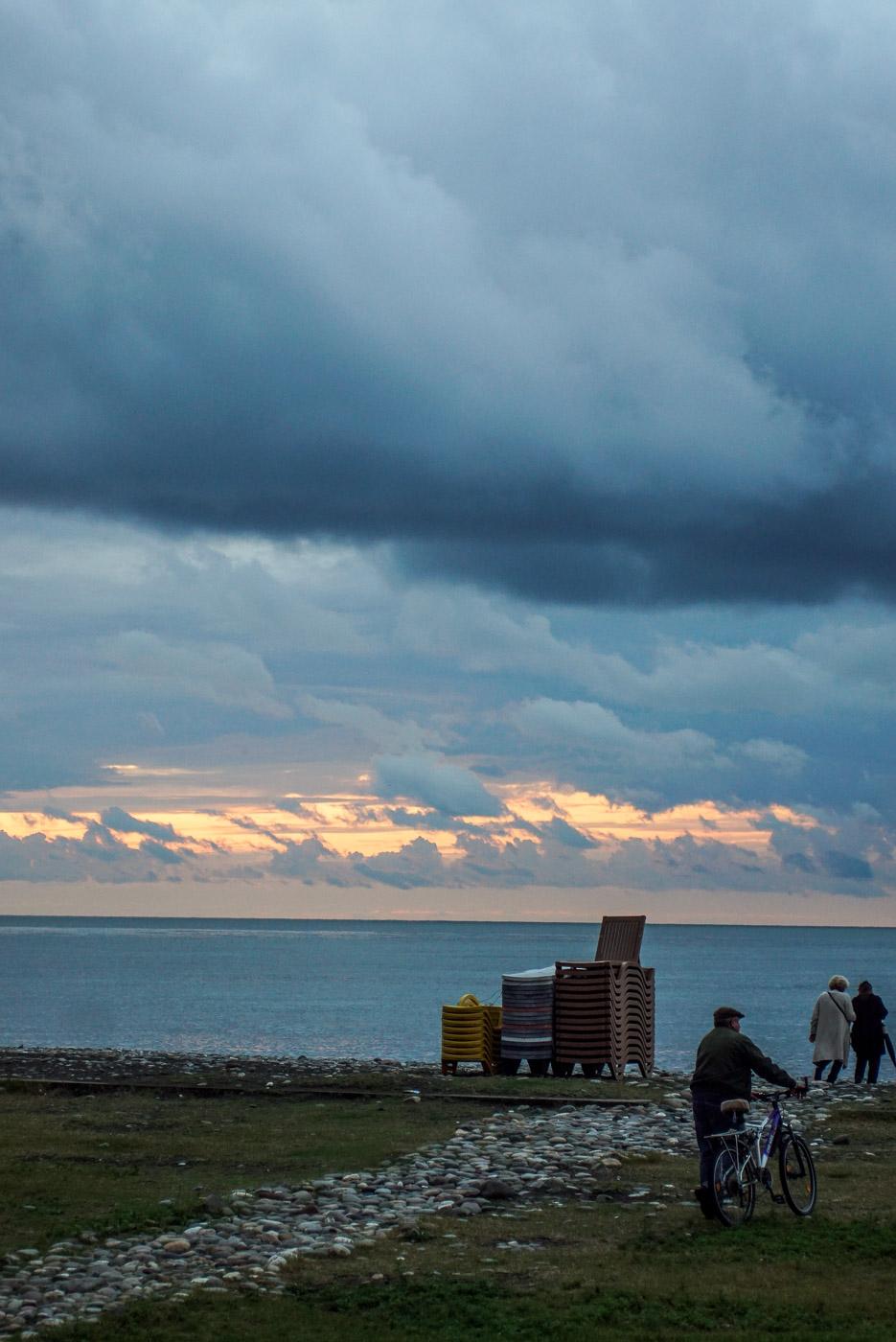 Zu sehen ist wie die Sonne untergeht und die dichten Regenwolken teilweise rot gefärbt sind. Im Vordergrund führt ein steiniger Weg zum Strand auf der einen Mann mit alten Fahrrad läuft.