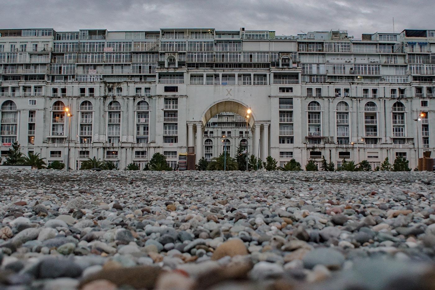 Zu sehen ist von Bodennähe aus aufgenommen ein Blick auf das Eingangstor des vielleicht größten Hauses von Batumi. Über 120 m breit und zunächst 7 Stockwerke hoch. Man kann deutlich erkennen, dass danach noch weitere fünf Stockwerke aufgebaut wurden. Ein beeindruckendes Gebäude