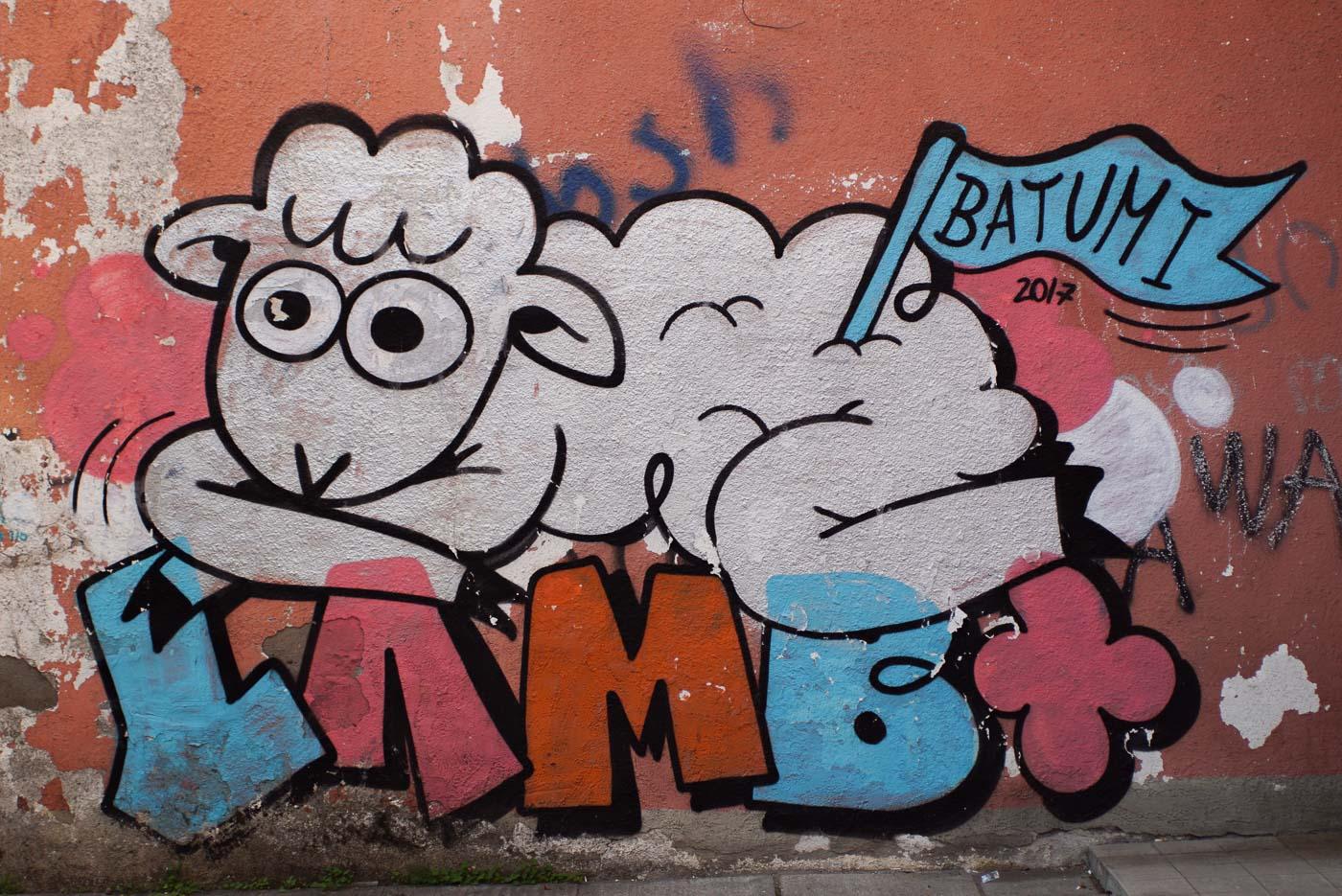 Zu sehen ist ein Graffiti Schaf das auf dem Schriftzug Lamb liegt. In dem hinteren Ende seines Felles steckt eine blaue Fahne mit der Aufschrift Batumi.
