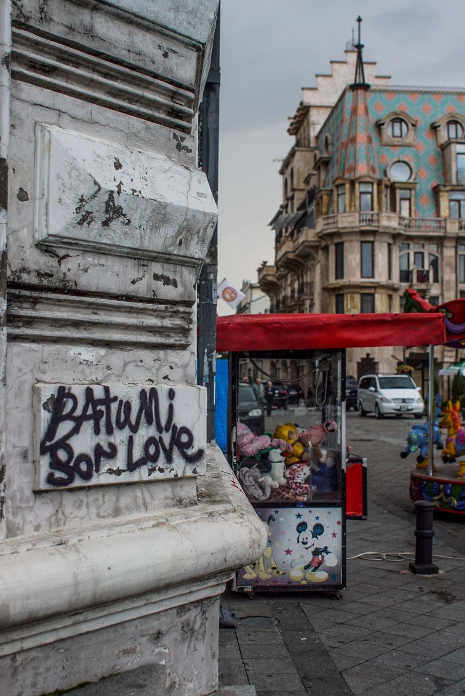 Von einer Ecke aus ist wieder der Blick auf das Gebäude zu sehen, an der Ecke selbst, ist ein Graffiti zu sehen wo draufsteht Batumi sor love.