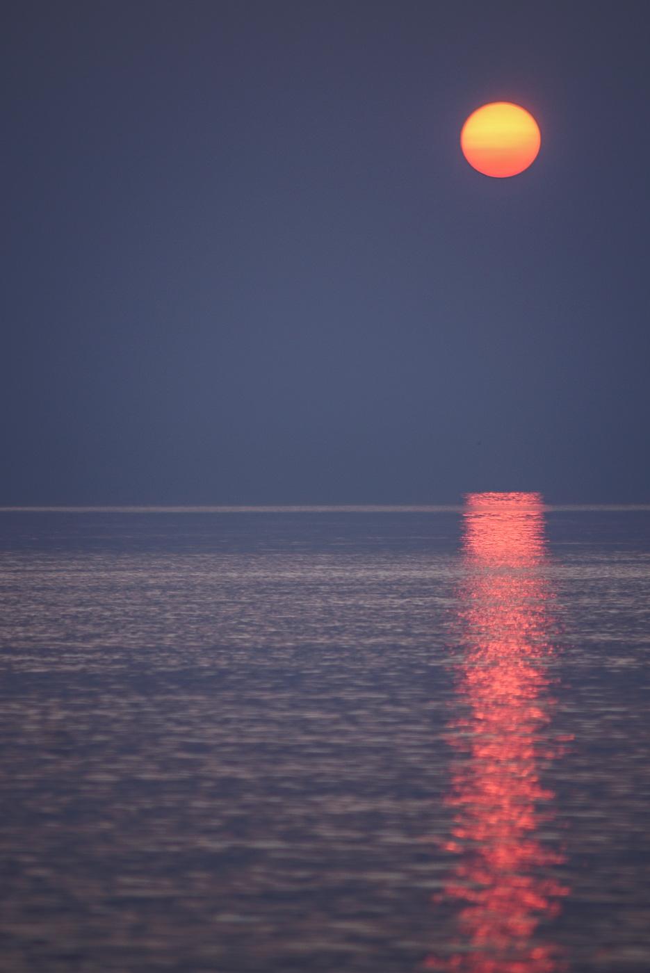 Zu sehen ist, wie die Sonne über einem spiegelglatten Meer untergeht,in diesem Spiegel sie sich orange rot wieder.