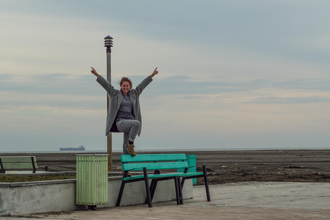 Zu sehen ist, die noch nicht fertiggestellte Strandpromenade in der Nähe von Poti. Lea steht mit einem Fuß auf der Rückenlehne einer türkisenen Bank, mit gleichfarbigem Mülleimer daneben. Sie streckt die Hände zum Himmel und lächelt in die Kamera. Gleich daneben ist eine weitere Sitzbank mit passendem Mülleimer in mintgrün zu sehen, hinten am Horizont fährt ein Containerschiff.