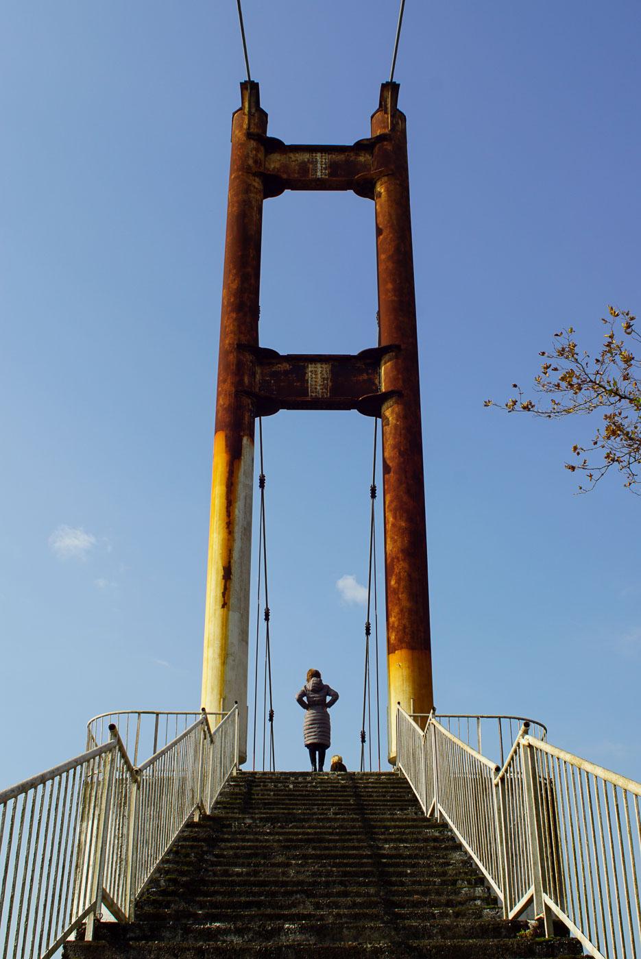 Zu sehen ist, der Aufgang zu einer Hängebrücke. Die Pfeiler sind stark verrostet, oben am Treppenabsatz stehen Luk und Lea.