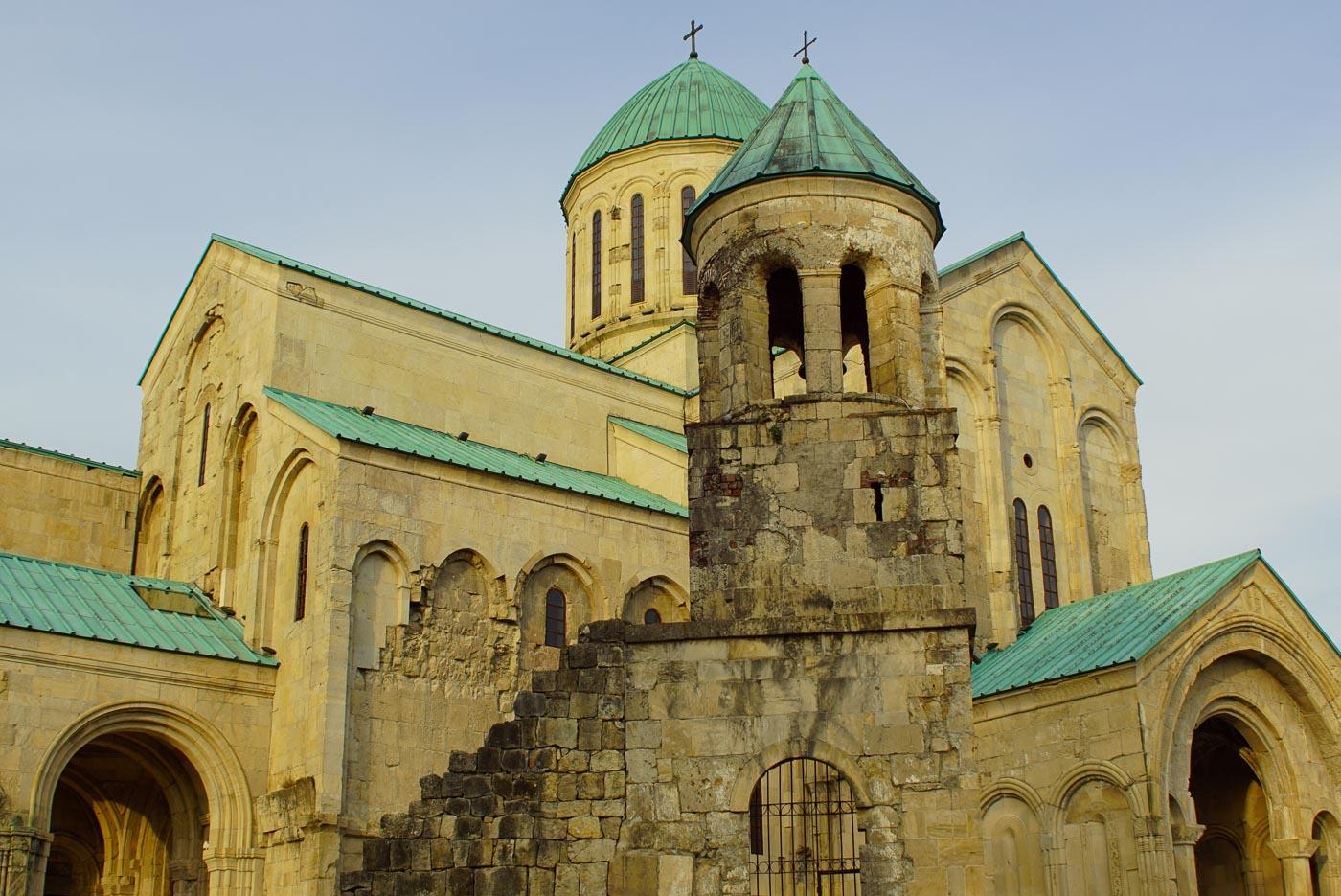 Zu sehen ist die Kathedrale von Kutaisi mit ihrem sandsteinfarbenem Gemäuer und Kupfer Grünen Dächern.