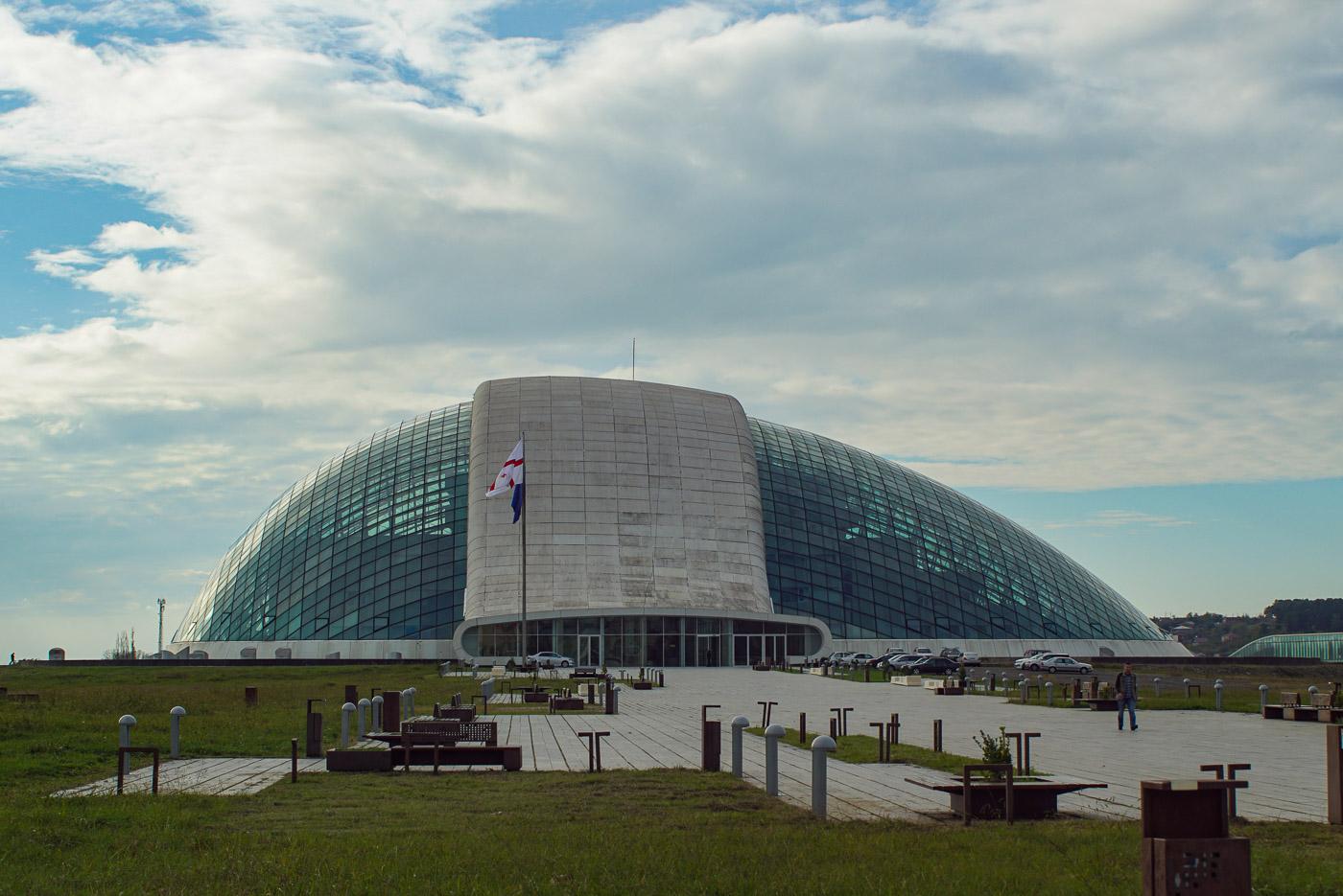 Zu sehen ist das futuristische Parlamentsgebäude in tiblissi es hat die Form eines halben Ei´s was auf der Seite liegt und von einem Betonstreifen umfasst wird. ansonsten ist es verglast und im Inneren erkennt man die einzelnen Gebäude.