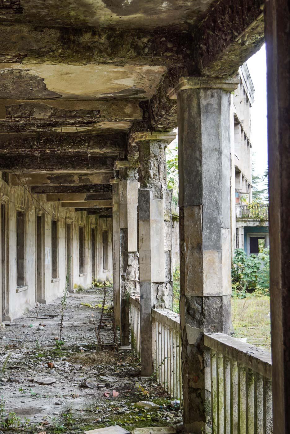 Zu sehen ist die außen Galerie eines bogenförmigen Sanatoriums. Überall bröckelt der Putz von den Wänden der sich am Boden sammelt, vereinzelt wachsen größere Pflanzen aus dem Boden.