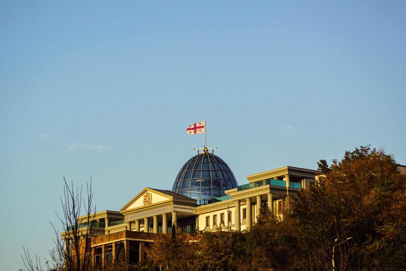 Zu sehen ist der Präsidentenpalast in Georgien Tbilisi. Auf seiner gläsernen Kuppel, ähnlich der des Reichstages, weht die georgische Flagge. Das ganze Gebäude ist in ein wunderschönes Licht durch die untergehende Sonne getaucht.