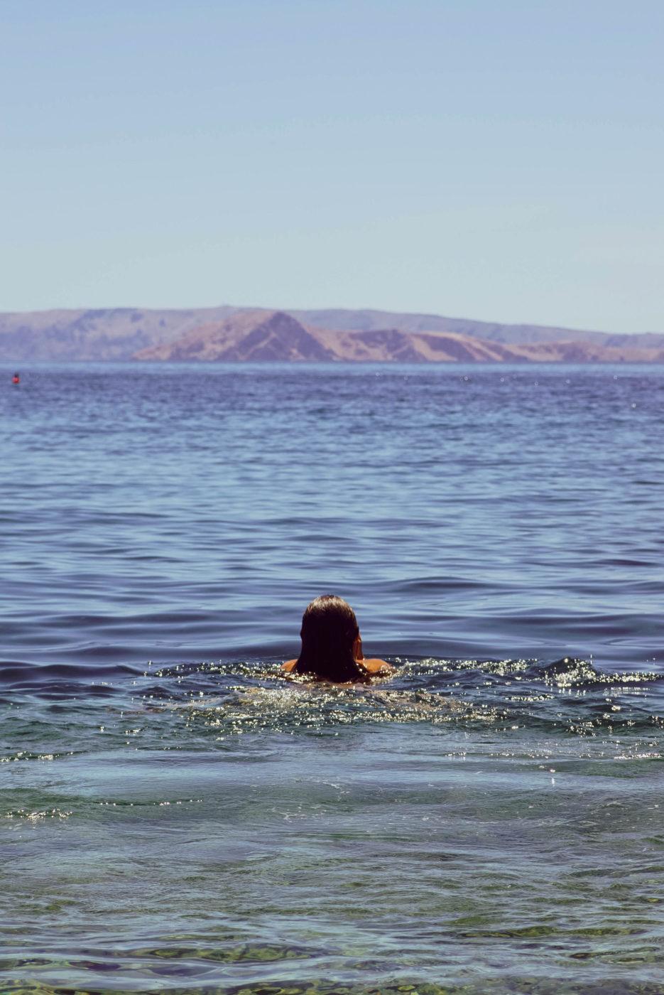 Lea schwimmt bei Sonnenschein aufs Meer hinaus. Im Hintergrund ist die Küste einer Insel zu sehen.