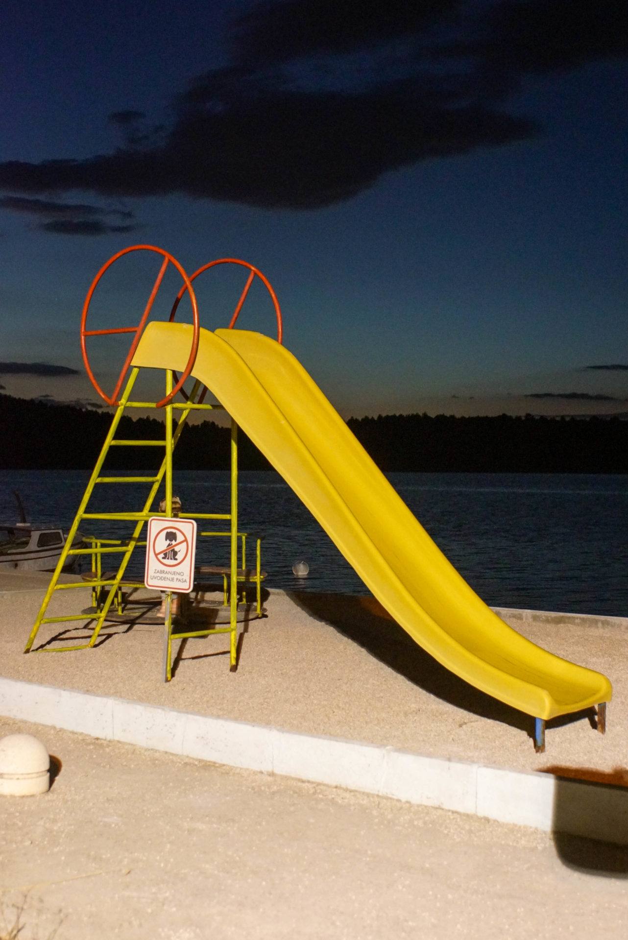 Im Vordergrund ist eine alte gelbe Rutsche hell erleuchtet zu sehen. Der Hintergrund ist dunkel, zeigt aber noch Restlicht vom Sonnenuntergang