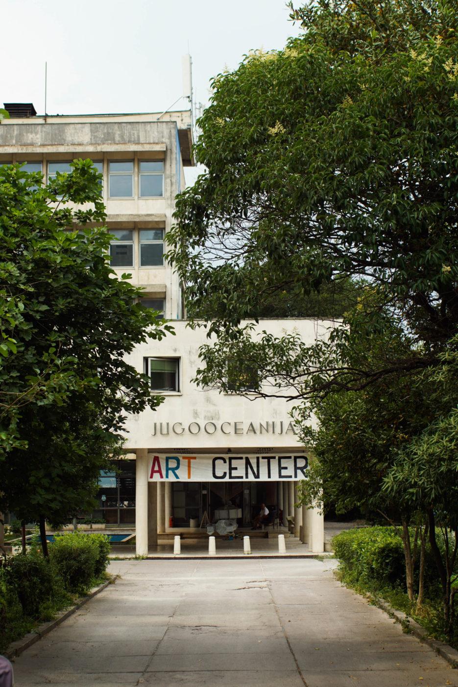 Man blickt durch eine Allee auf das dukley art-center, einem klassischen dreistöckigen Plattenbau. Über dem Eingang hängt ein Transparent bei dem mit verschiedenen Farben und per Hand der Schriftzug Art Center aufgemalt wurde.
