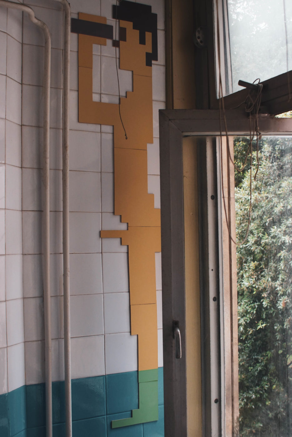 Auf der gekachelten Wand einer Toilette wurden ein Mann aus Holz in Form von Computerpixeln angebracht. Er hält sich ein Fernglas vor dei Augen und sein Penis steht wagrecht von ihm weg