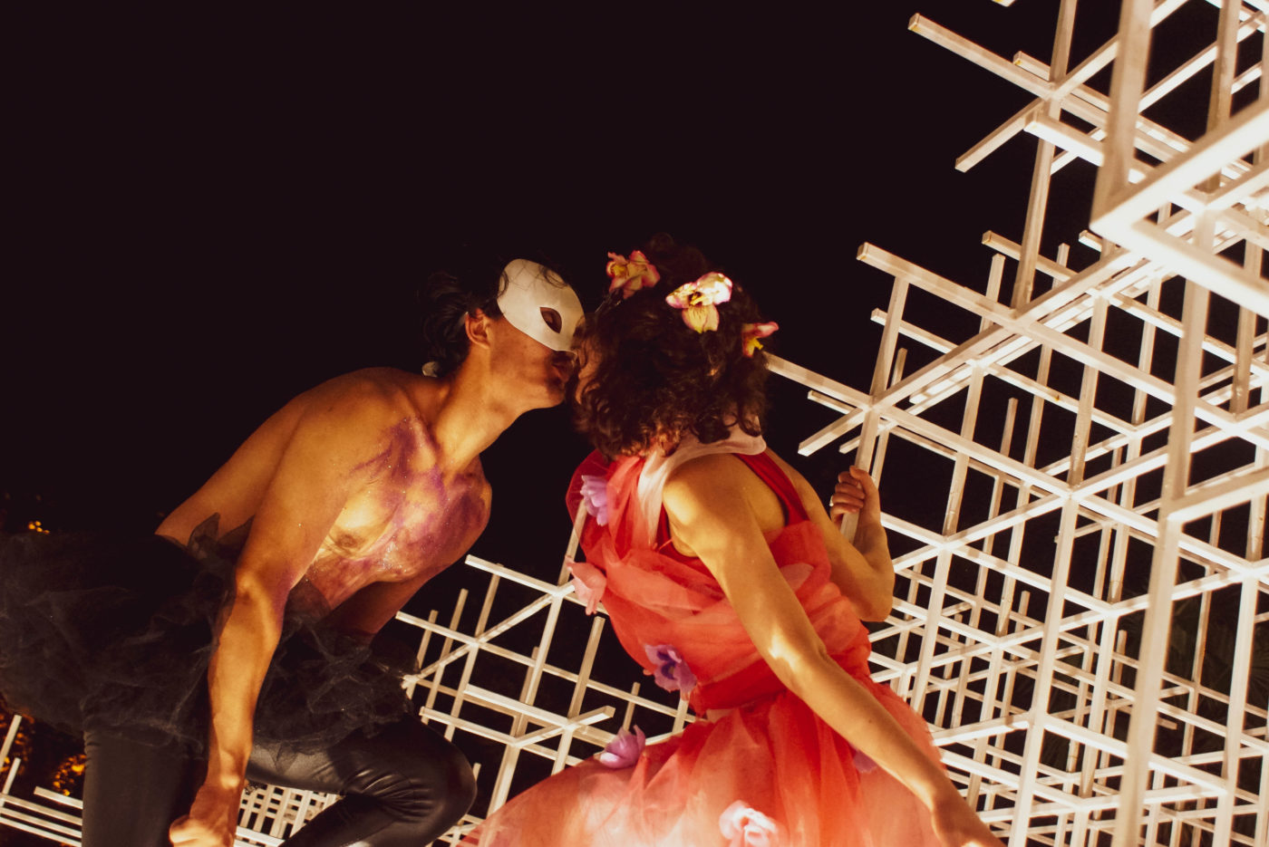 Eine weibliche und ein männlicher Schauspieler mit nacktem Oberkörper und weißer phantom der oper Maske küssen sich auf einem weißen streben Gerüst. der Hintergrund ist pech schwarz
