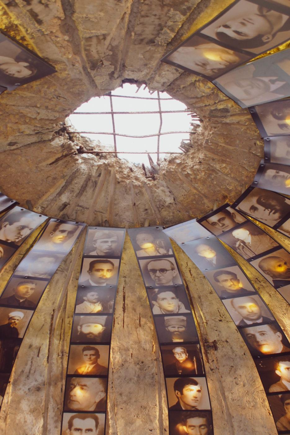 Zu sehen ist der Eingang des Bunkermuseums in Tirana von Innen. An der Bunker decke ist ein Loch im Stahlbeton. Sternförmig von diesem laufen Fotos mit den Opfern von der Decke