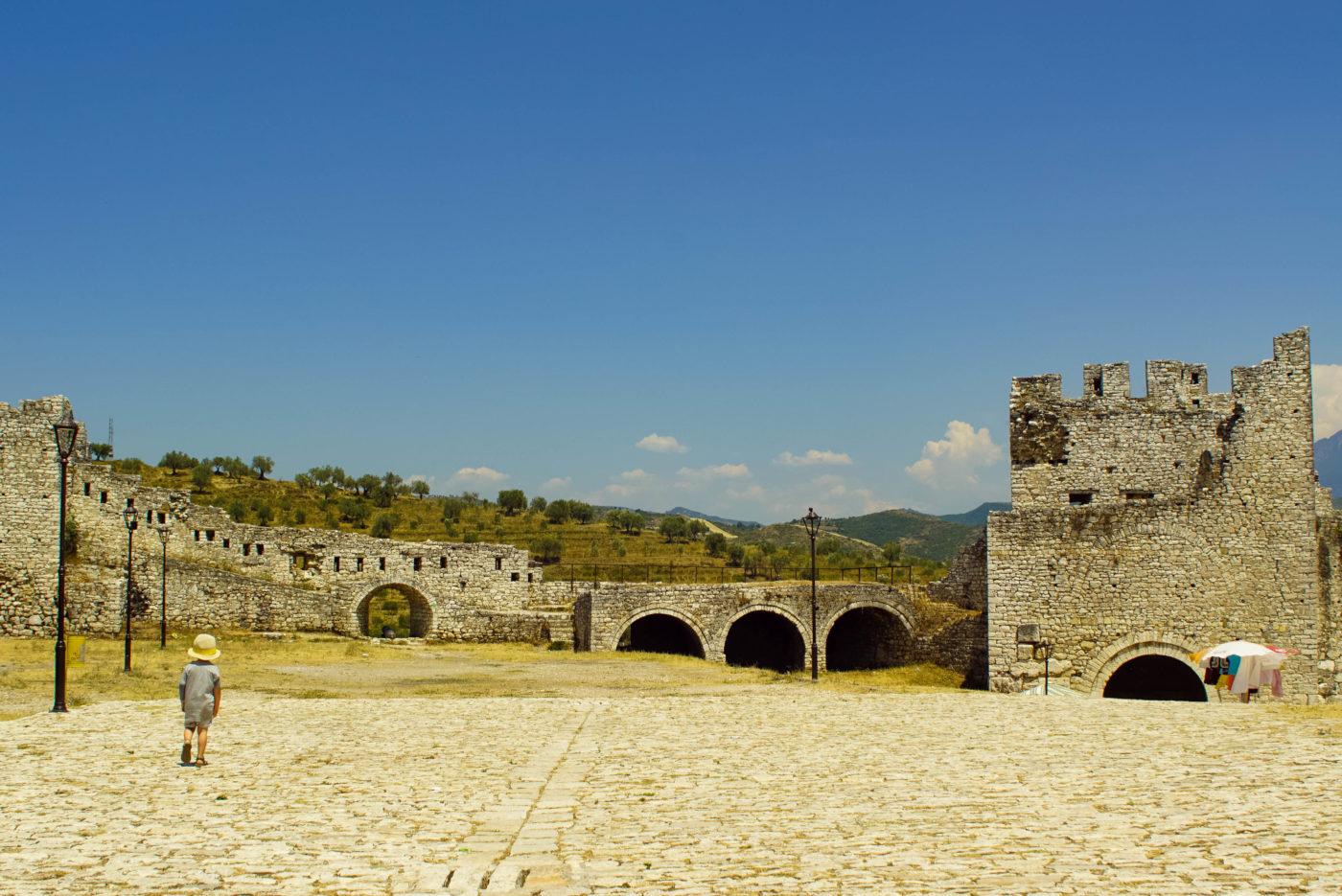 Zu sehen ist wie Luk über einen Leeren Platz vor einem der mächtigen Tore der Festung läuft.