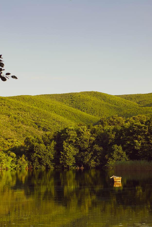 Es ist ein kleiner See zu sehen in dem sich die grünen Hügel im Hintergrund spiegeln, auf ihm schwimmt ein einzelnes altes Holz Ruderboot