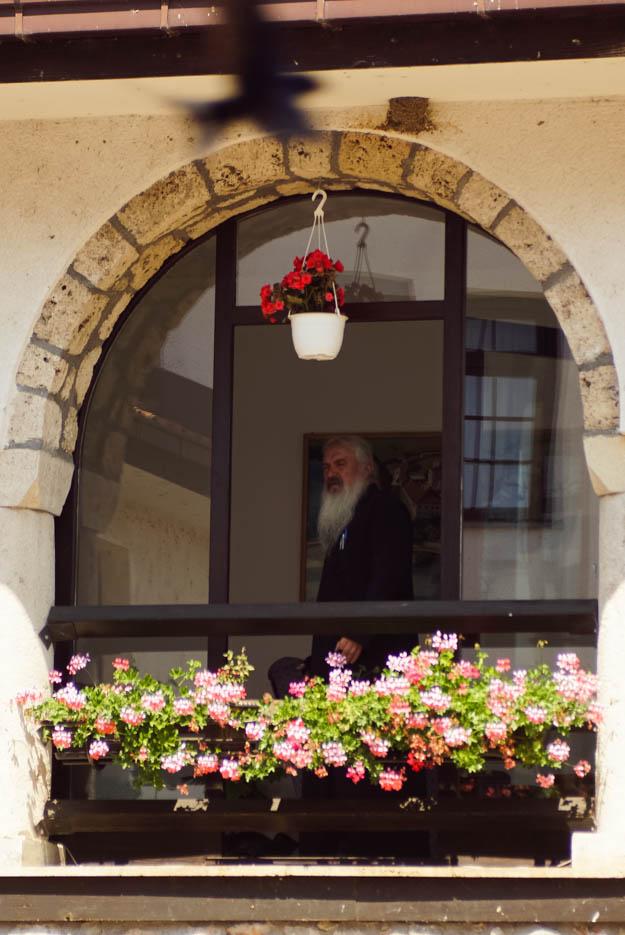 Zu sehen ist ein bogenförmiges Fenster aus dem ein Mönch mit langem weißem Bart schaut. Vor dem Fenster ist ein großer Blumenkasten mit Geranien angebracht von der Decke hängt noch ein Topf mit roten Blumen.