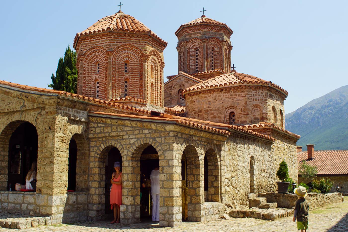 Im Vordergrund steht Luk mit Hut und blickt auf die Kirche von Sveti Naum. Lea steht in einem der Bögen und blickt lächelnd zu Luk