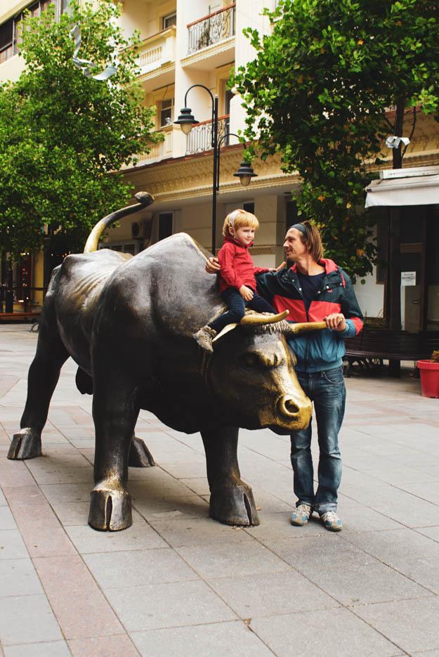 Zu sehen ist ein lebensgroßer bronzener Stier auf dem Luk sitzt, Paul steht daneben legt den Arm und ihn und blickt ihn an.