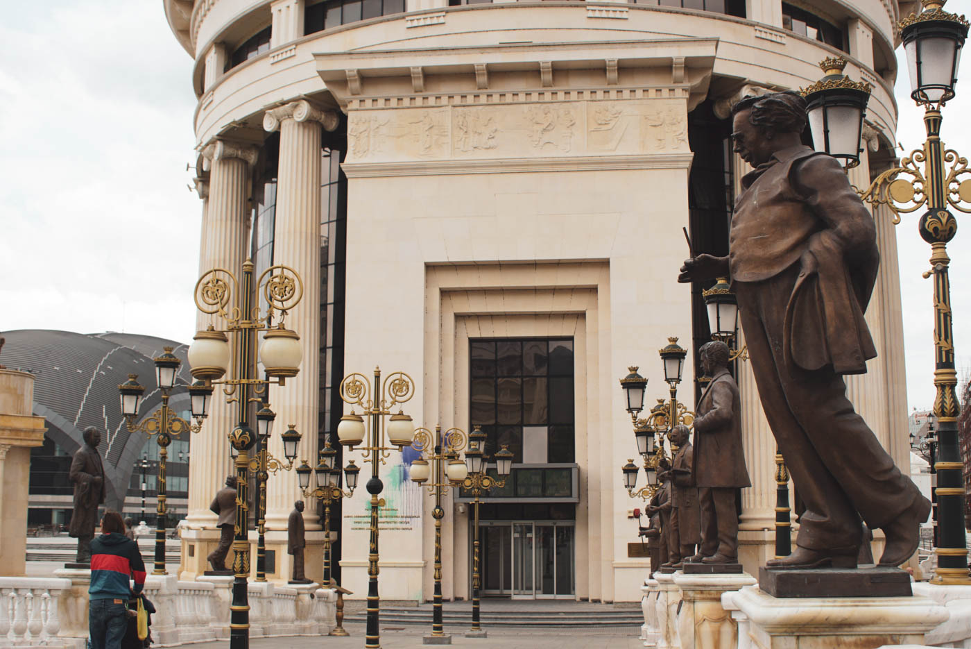 Zu sehen ist wie Paul mit Luke im Kinderwagen über eine Brücke läuft, an jedem Pfeiler der Brüstung der Brücke ist eine Bronzestatue von einem mehr oder weniger berühmten Mazedonier zu sehen. Im Hintergrund erhebt sich eines der pompösen Regierungsgebäude das mit Farbbeuteln beworfen wurde.