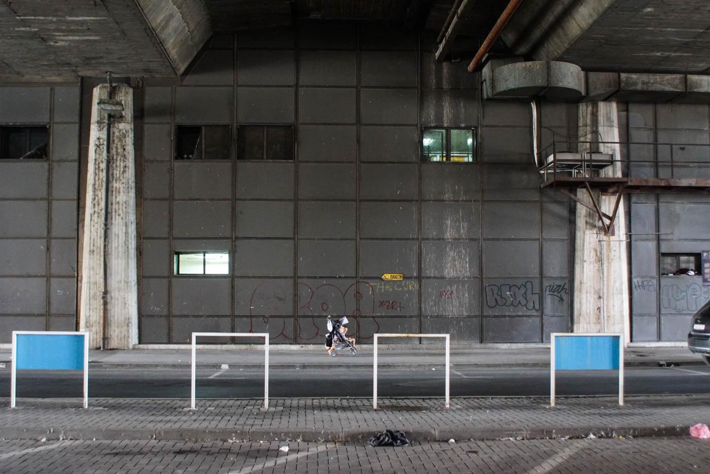 Eine große graue Unterführung ist zu sehen in der Mitte weit entfernt sitzt Luk und Blick zur Kamera
