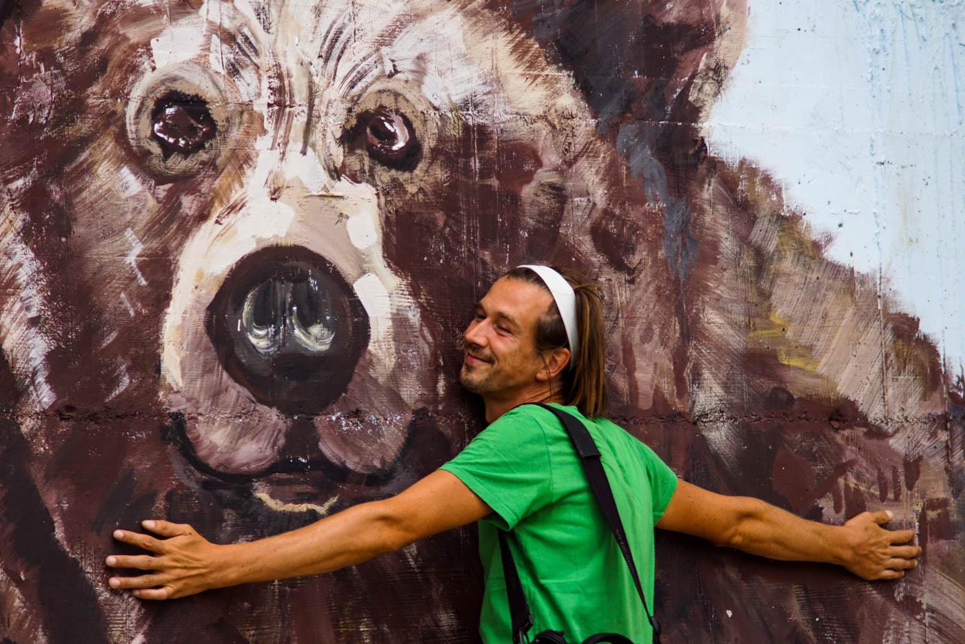 Es ist ein übergroßer Bär an eine Wand im Bären Sanatorium in der Nähe von Pristina gemalt. Paul lehnt sich an die Wand und umarmt den Bären lächelnd