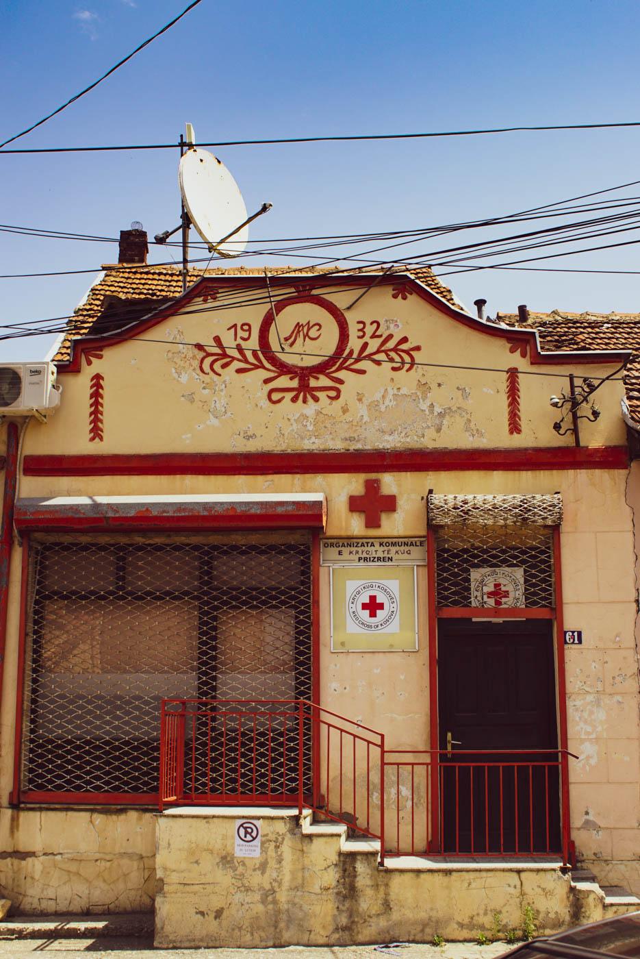 Ein altes Haus von 1932 mit Roten Kreuz Schild und roten Fenster Türrahmen und Treppengeländer