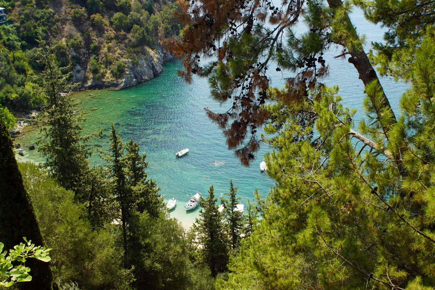 Blick durch einen bald auf eine typische griechische Bucht mit türkisfarbenen Wasser das langsam dunkler wird. In der Bucht schwimmen ein paar Leute und es sind ein paar kleine Boote am Strand zu sehen