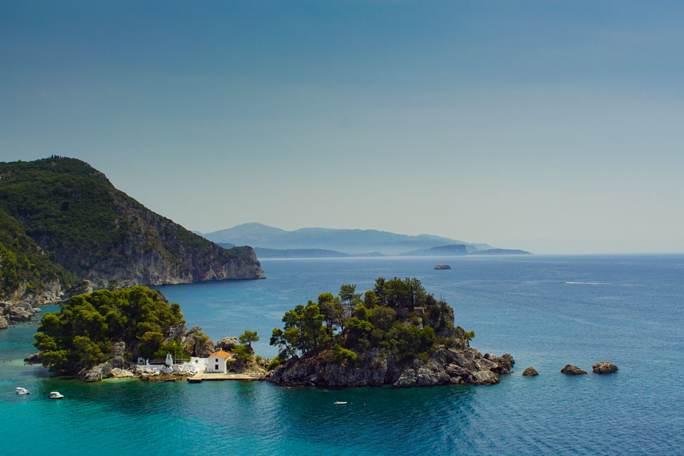 Blick auf eine griechische Bucht, in der eine kleine Insel mit einem weißen Haus und Bootsanleger sich befindet. Im Hintergrund sind im Dunst noch weitere Berge der Küste zu erkennen