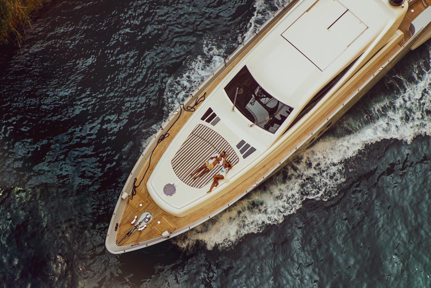 Blick von einer Brücke nach unten in den Kanal von Korinth es zieht eine Luxusyacht in Nahaufnahme vorüber. Auf ihrem Sonnendeck, vorne am Bug, liegen einem Mann und eine Frau und blicken nach oben in die Kamera