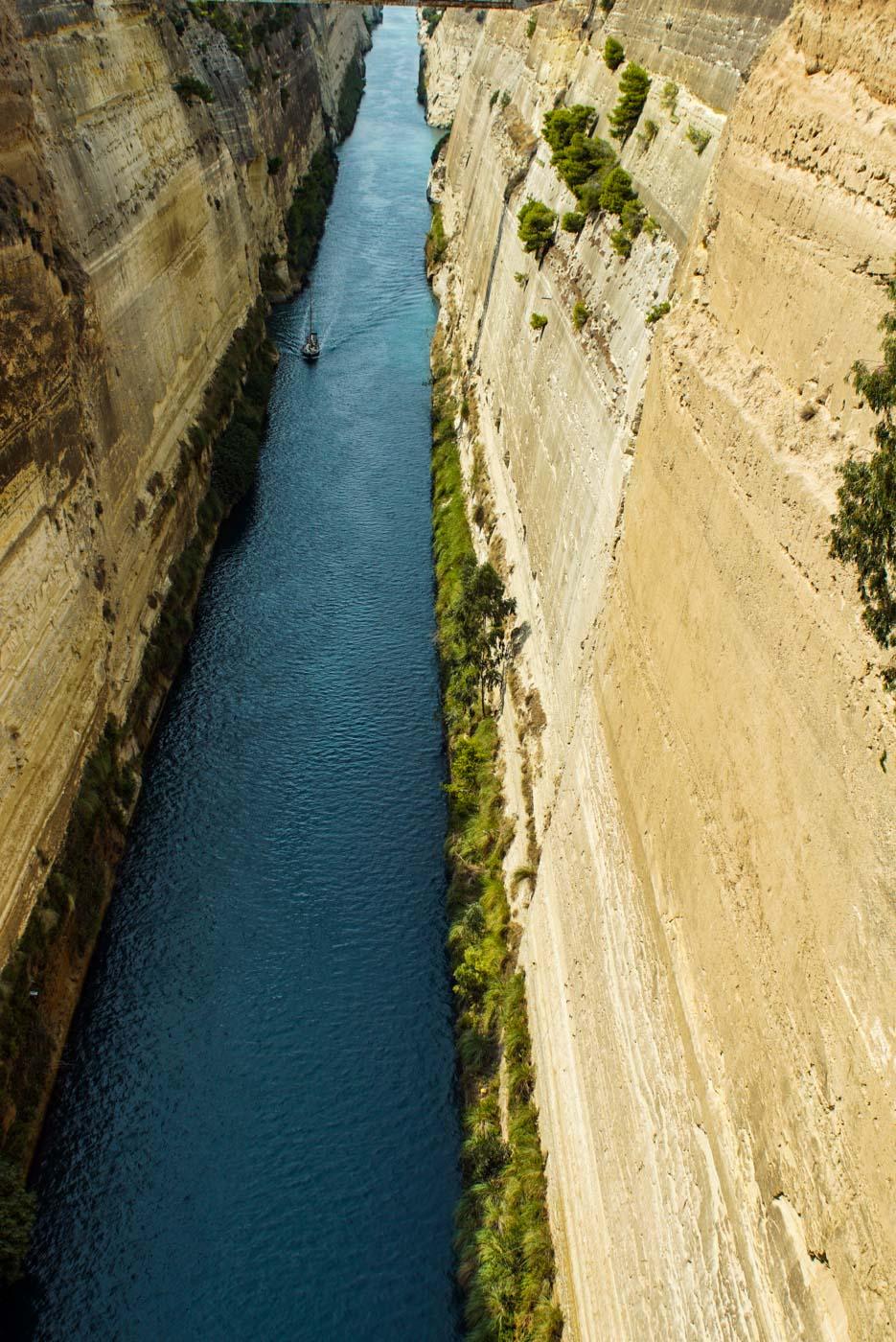 Blick in den 80m tiefen Kanal von Korinth. Die Steilwände sind zu erkennen, an denen teilweise Bäume herauswachsen, ganz hinten sieht man wie sich ein kleines Segelboot.