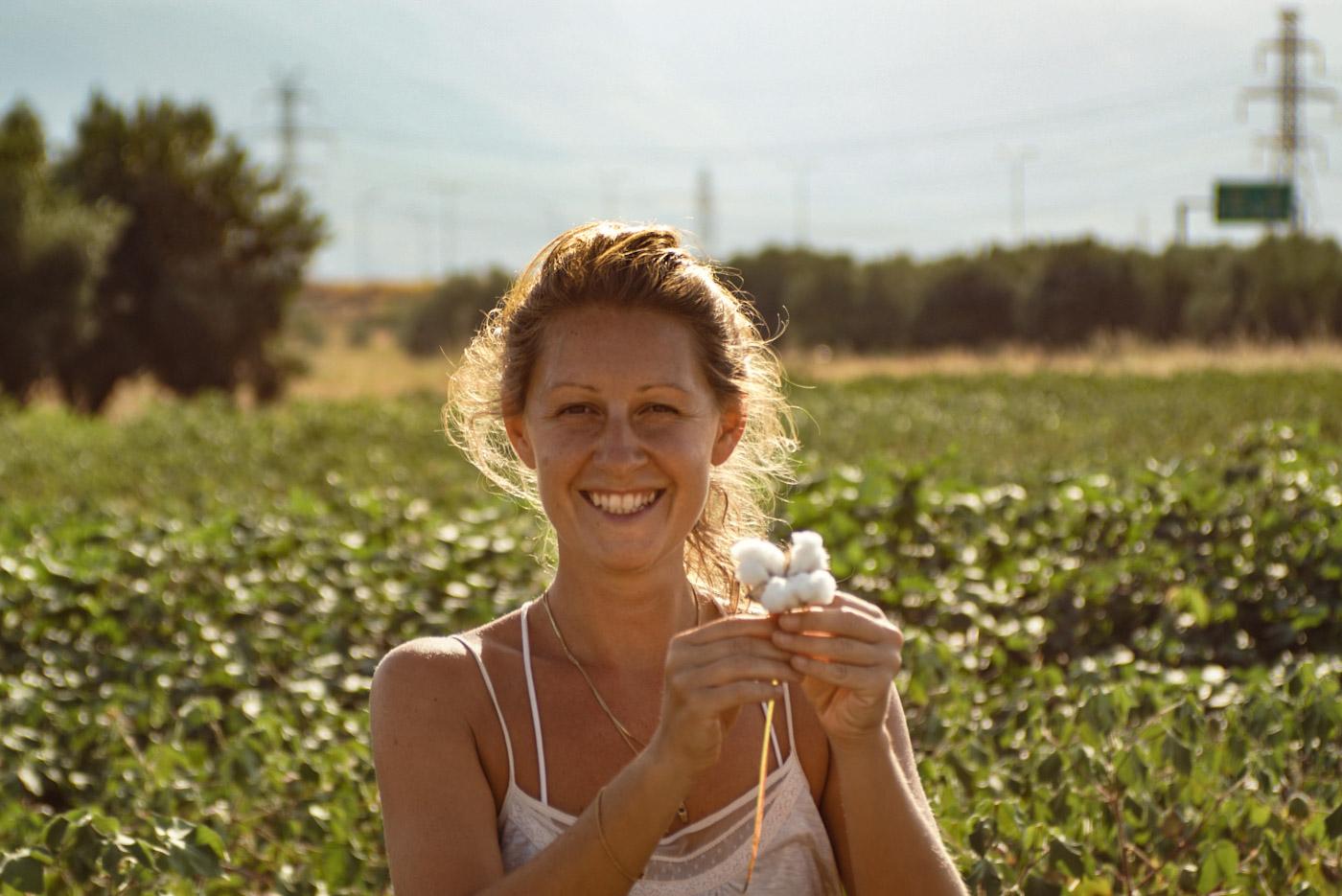 Lea lächelt strahlend in die Kamera und hält ein Stück Baumwolle in die Höhe hinter ihr ist das Feld zu erkennen wo sie die Baumwolle gepflückt hat