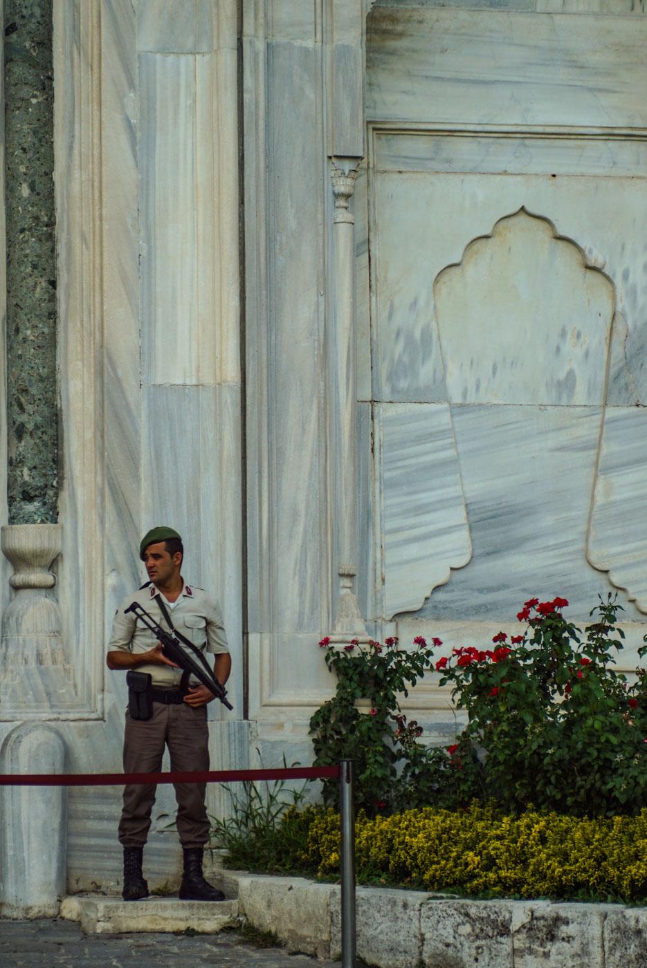 Das Bild zeigt einen Wachmann in der Nähe der Hagia Sophia wie er nach rechts guckt. Dadurch sind die zwei Männer die vor dem secondhand BH Laden sitzen von den Soldaten eingerahmt die sie beobachten.