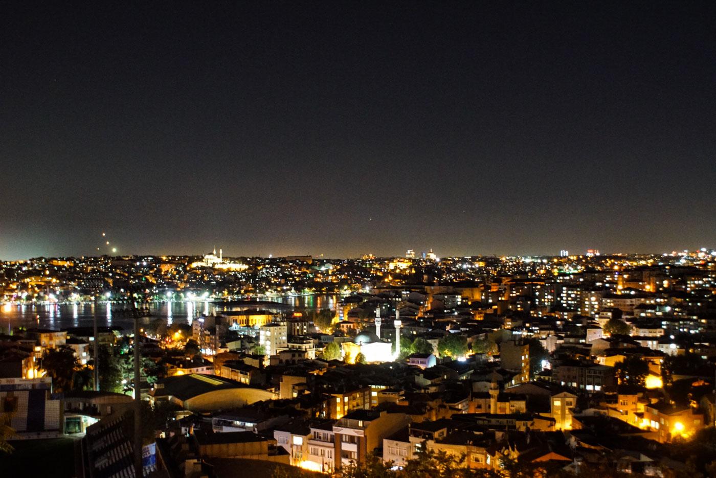 Blick von einer erhöhten Position auf die Stadt Istanbul bei Nacht. es sind mehrere erleuchtete Moscheen zu sehen sowie der Bosporus und viele Häuser die in ihren Lichtern strahlen.