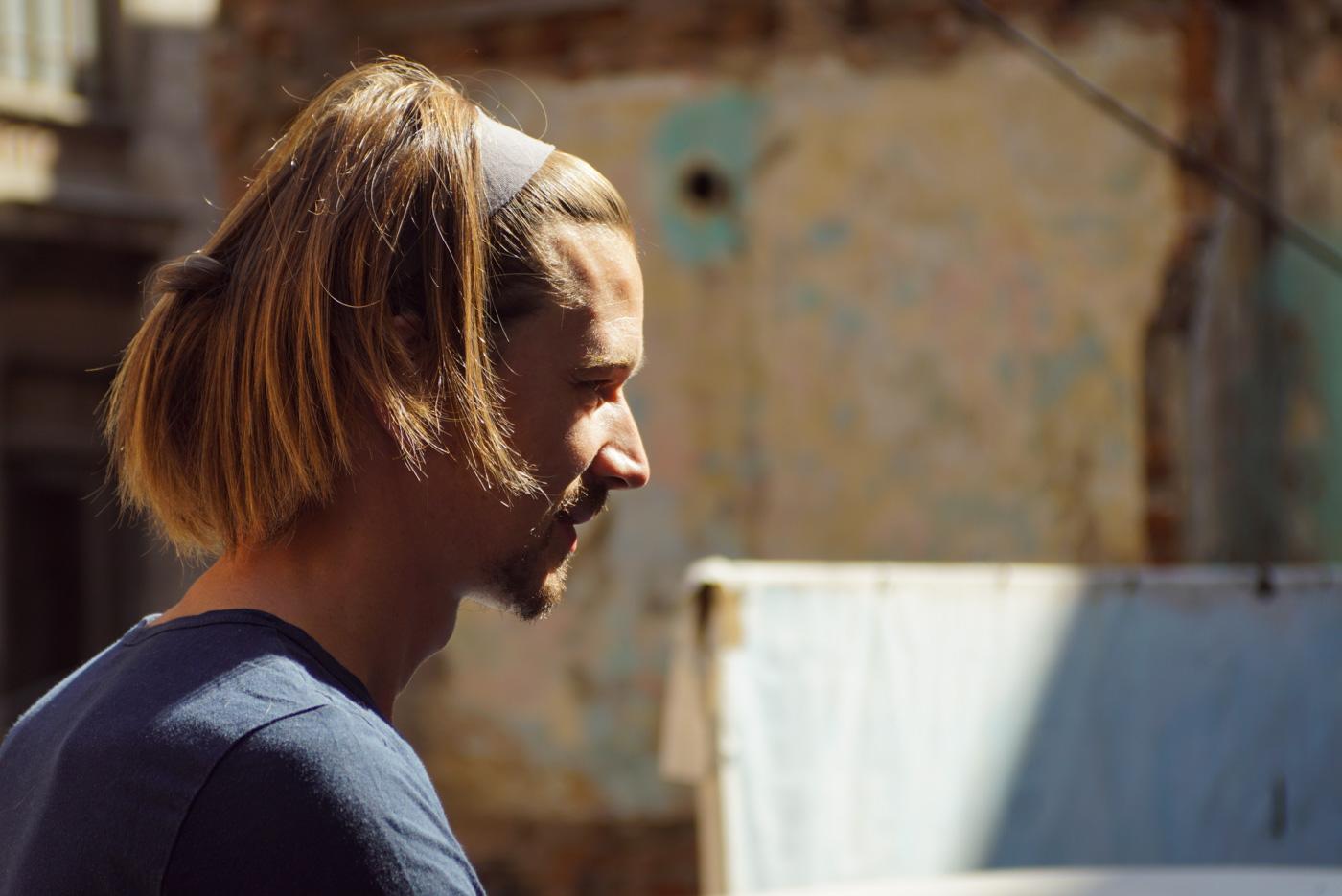 Nahaufnahme von Paul erträgt hat lange Haare und ein Stirnband und ist aus dem Profil zu sehen.