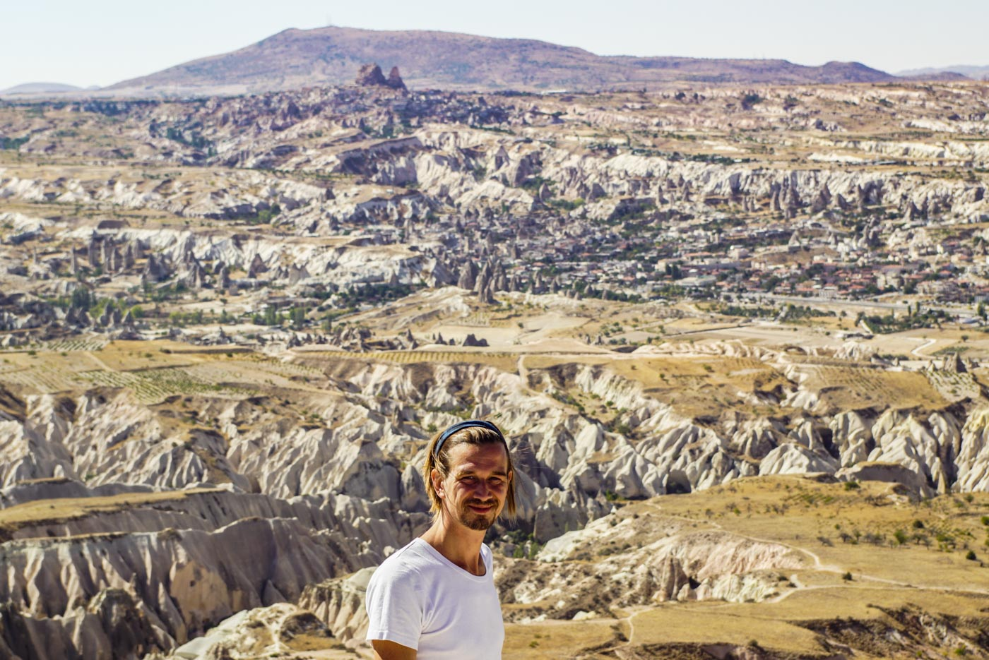 Paul steht auf einem Berg und blickt in die Kamera im Hintergrund ist die wunderschöne zerfurchte kappadokische Landschaft mit ihren Zuckerhüten und Tälern zu erblicken.