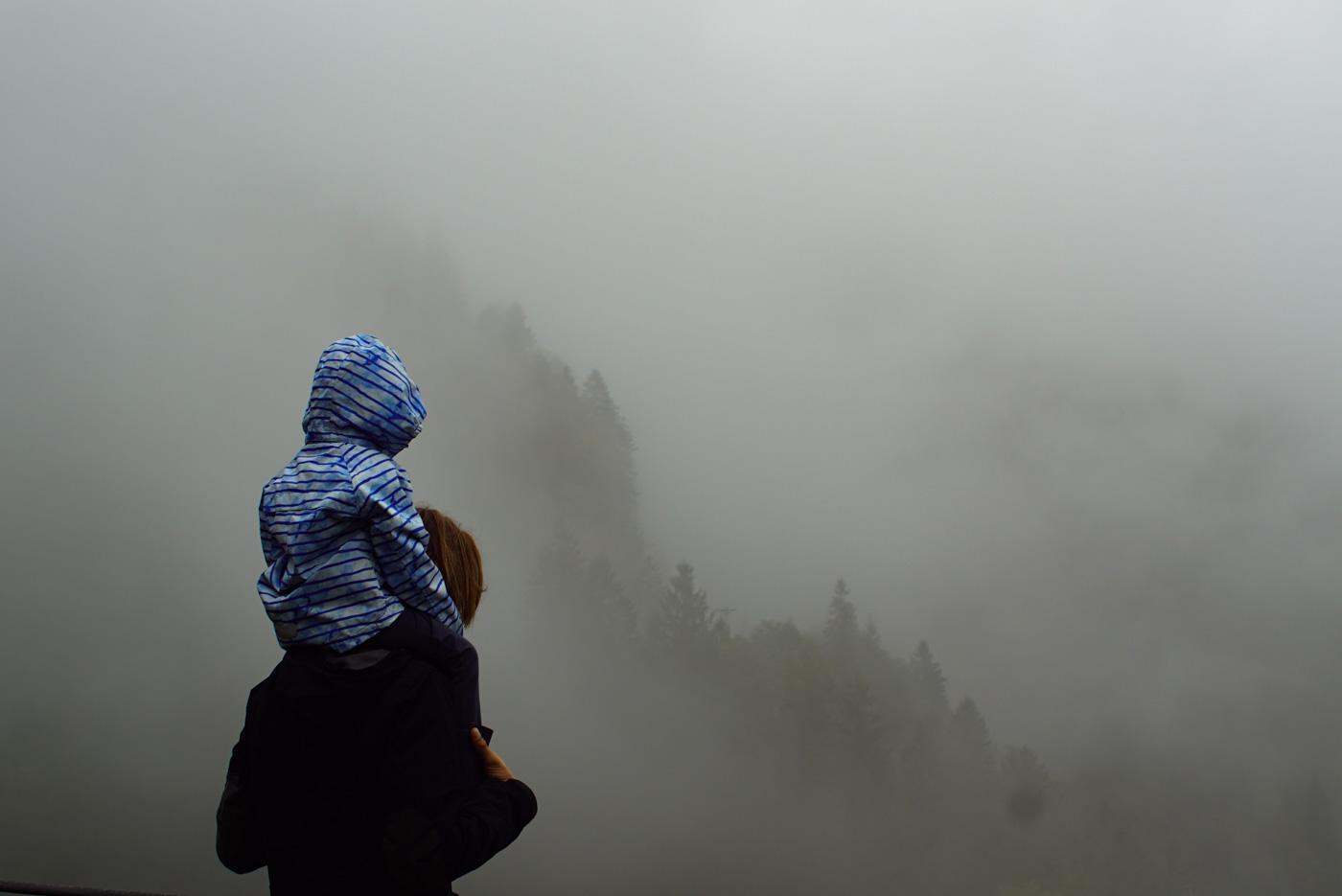 Paul trägt Luk auf den Schultern und beide haben Regenjacken an. Der Hintergrund ist sehr neblig es zeichnet sich aber ein ein mit Bäumen bestandener Berghang durch die Wolken ab.