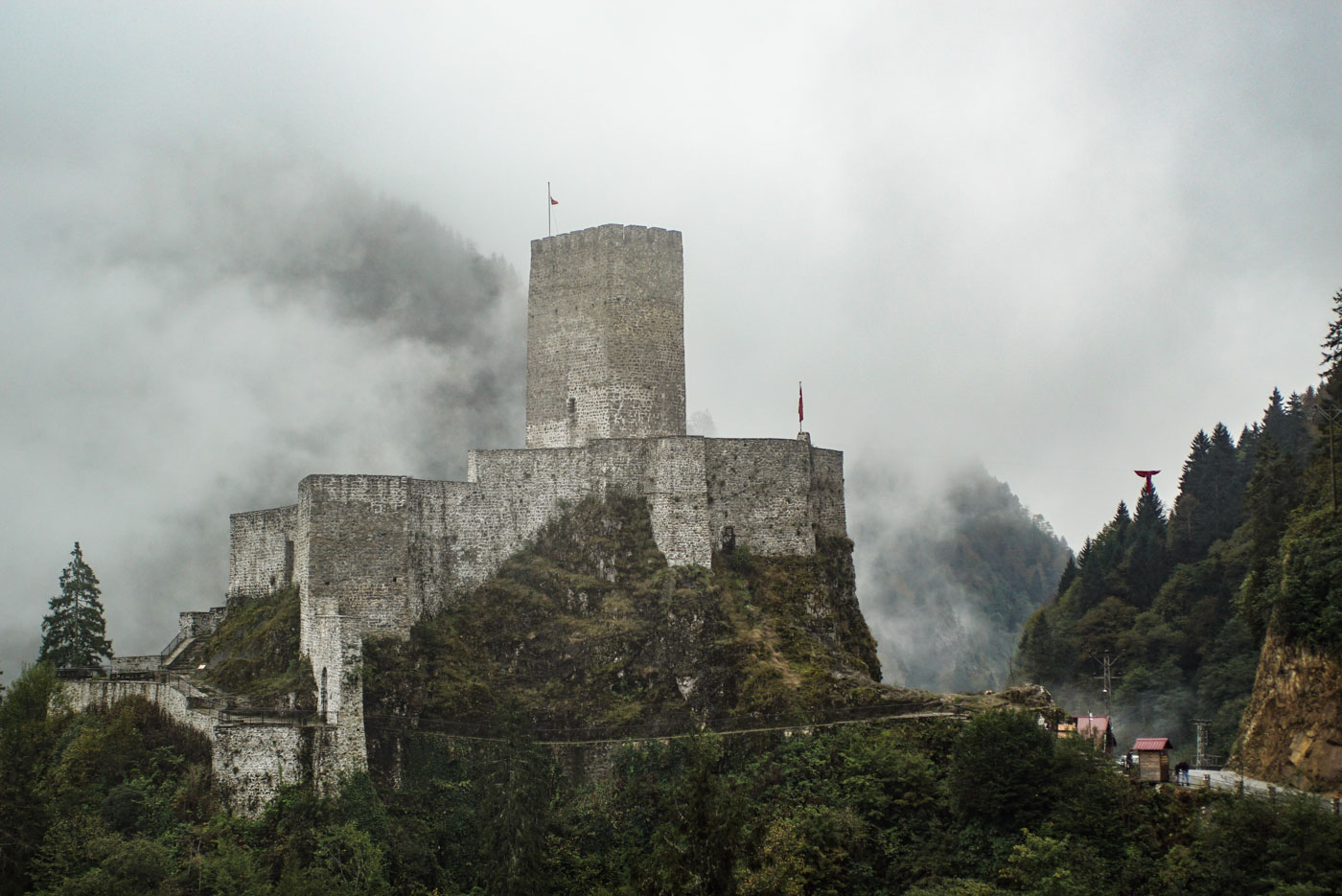 Zu sehen ist eine mittelalterliche Burg die sich auf einen Felsgrat festhält. Der Bergfried erhebt sich meterweise in die Höhe der Hintergrund ist wolkenverhangen und vereinzelt ist der gegenüberliegende Berghang zu erkennen.