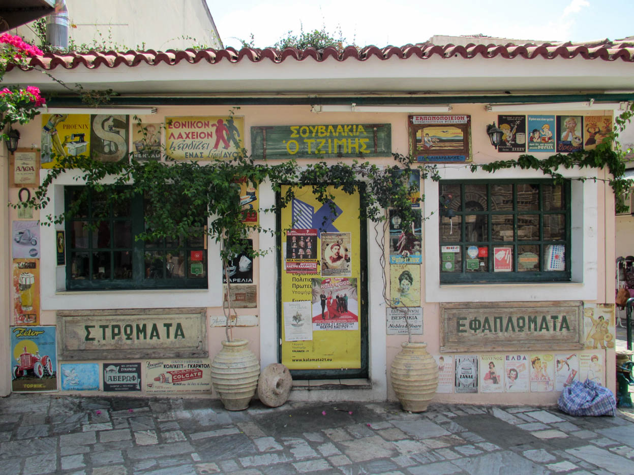 Eine kleine Ladenfront zwei Fenster und in der Mitte ist die Eingangstür. neben der Tür stehen zwei anbohren rechts und links aus der Efeu wächst alle anderen Freiflächen sind mithalten Lech Werbeschildern aus Griechenland bedeckt im Stil der 50er Jahre oder früher