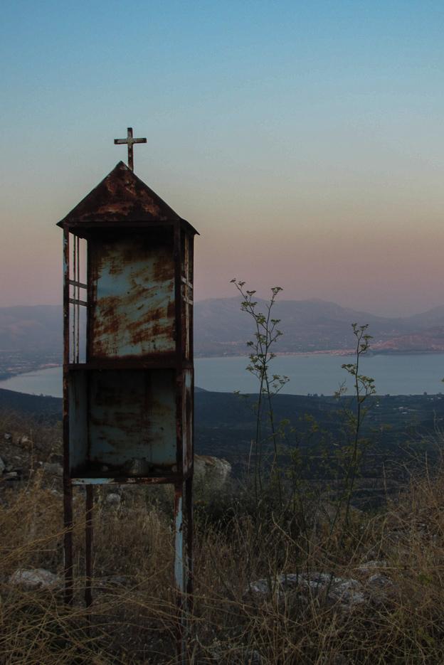 Im Vordergrund steht ein griechisch-orthodoxes Andenken schreien im Hintergrund erstreckt sich eine Bucht mit Bergen