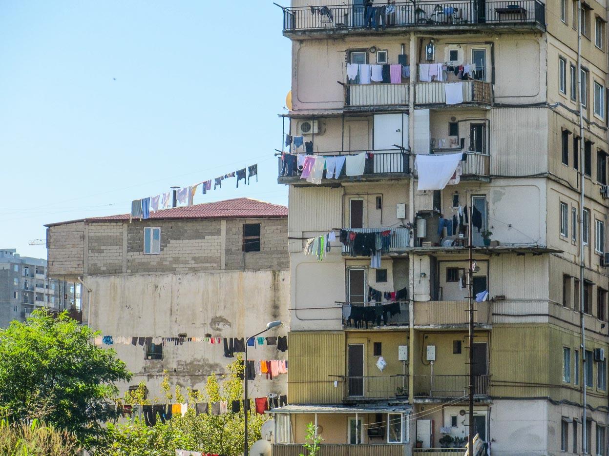 Zu sehen ist 1 mal am Plattenbau bei denen in der Sonne auf den Balkons überall Wäsche aufgehangen ist im Hintergrund sieht man einen weiteren Bau zudem über 20 m hinweg weitere Wäscheleinen gespannt sind.
