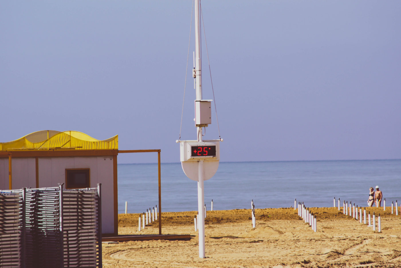 Ein Strand in Norditalien. im Vordergrund sind Stapel von Sonnenliegen zu sehen. In der Mitte ist ein Mast mitr einem Termometer zu sehen welches 25 Grad anzeigt. Dahinter sind unzählige Sonnenschirmständer zu sehen. Ein Paar läuft in Badesaachen von links nach rechts an der Waassergrenze entlang.