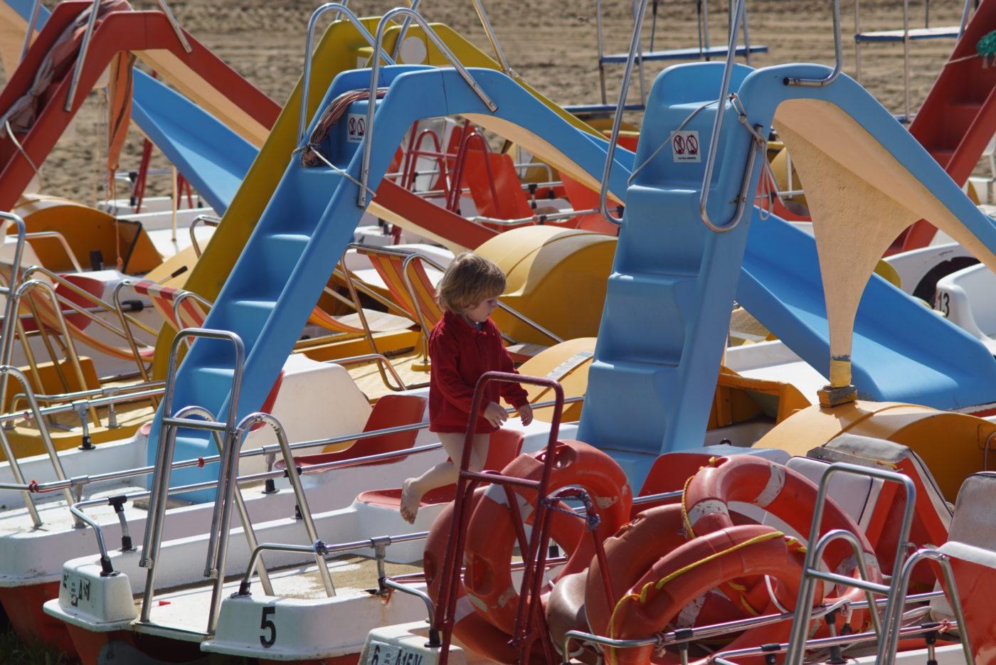 Es sind ca. zehn Tretboote mit Rutschen zu sehen die auf Sand am Strand liegen. Unser Sohn Luk hüpft in einem roten Langshirt von einem Boot zum anderen.