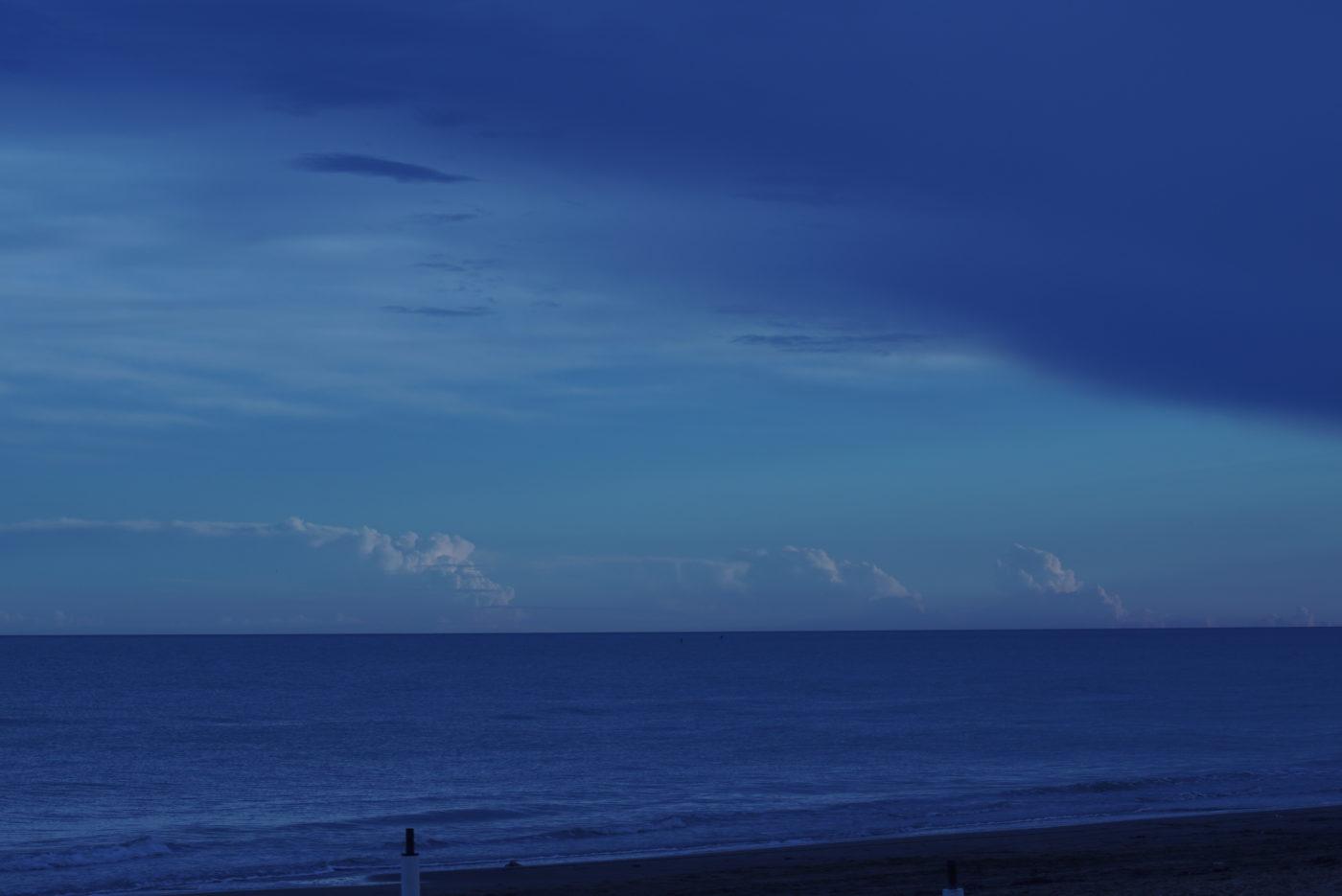 Das bild ist von vollen Blautönen geprägt. Im Vordergrund ist einstück Strand zu sehen und dahinter schließt die fast spiegelglatte Adria an. In der Ferne ist eine mächtige Wolkenbank zu sehen.