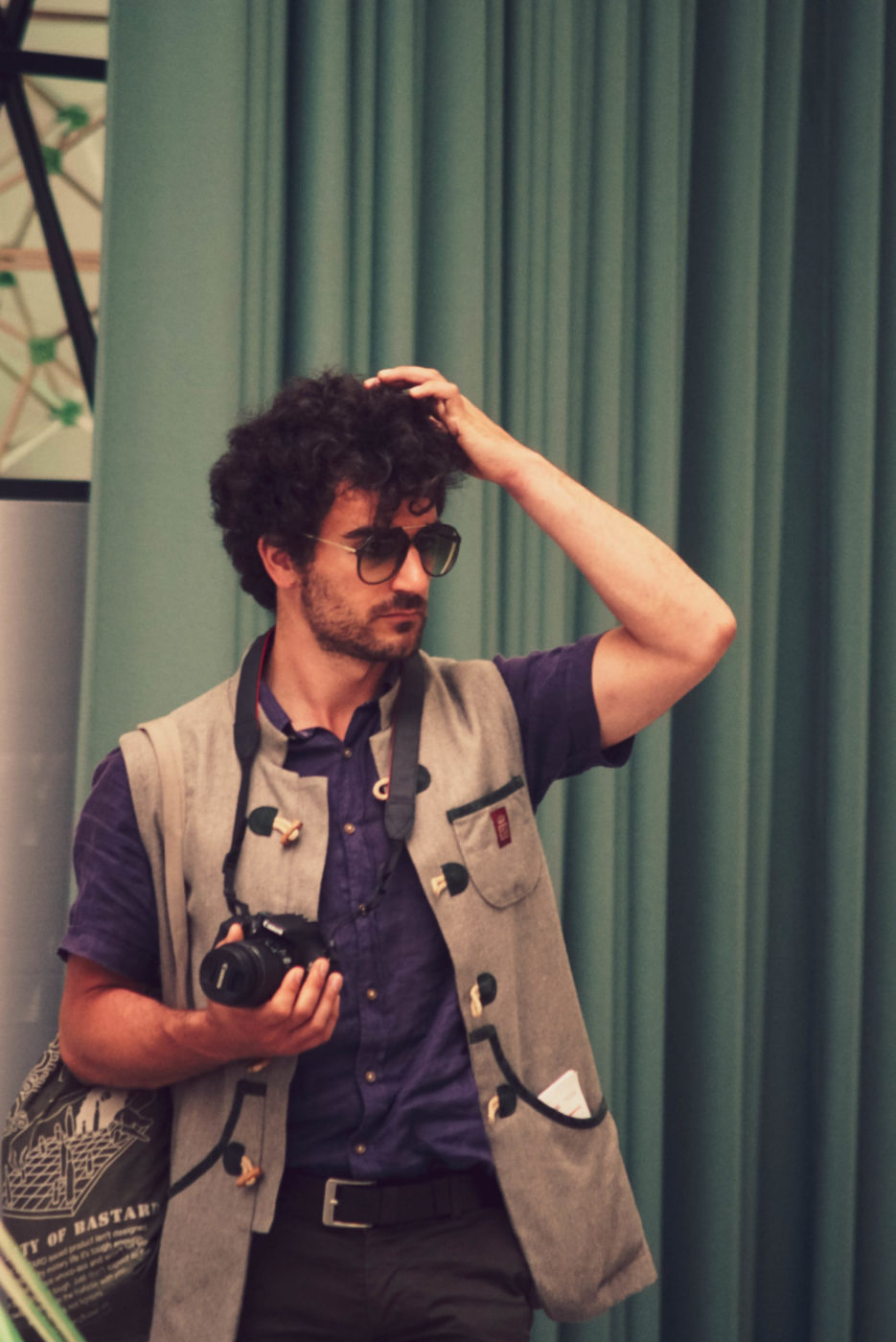 Ein Mann mit lila Hemd und beiger bayrischer Weste. Er hält eine Kamera in derr einen Hand und fährt sich mit der anderen Hand durch sein kurzes lockiges Haar