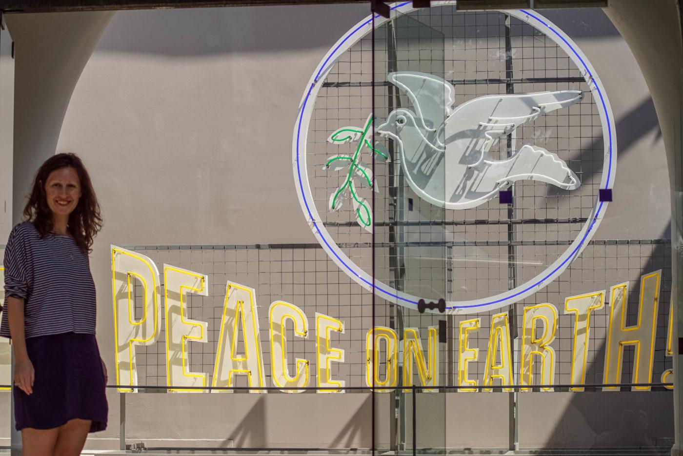 """Lea steht vor dem ungarischen Pavillon Eingang und lächelt frölich in die Kamera. Neben ihr ist aus dünnen Neonröhren eine weiße Taube mit grünem zweig zu sehen, sie umschließt ein gelber Kreis. Darunter ist der Schriftzug """"peace on earth!"""" zu lesen"""