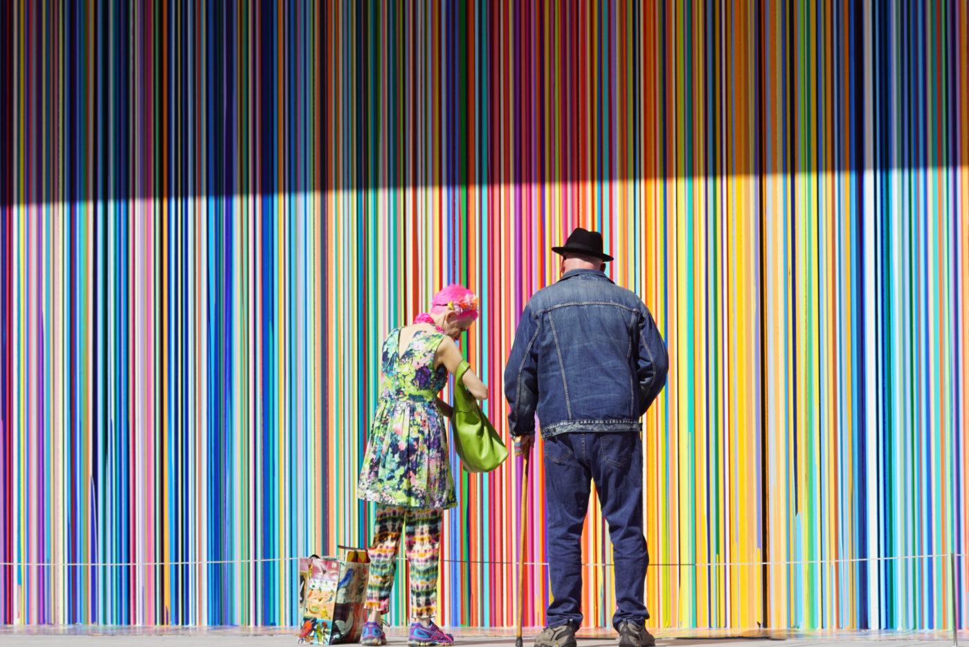 Im Hintergrund ist eine Wand mit vielen dünnen regenbogenfarbenen Streifen zu sehen. Davor steht ein Paar wie es unterschiedlicher nicht seinen kann. Sie in einem buntem Kleid und Hose die exakt die selben Farben wie die Wand im Hintergrund hat.Er komplett in Jeans gekleidet mit schwarzem Hut und Gehstock