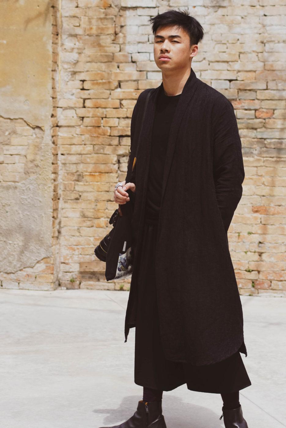Asiatischer Mann in schwarzem Stoffmantel. Er trägt eine Kamera mit Teleobjektive über der Schulter und Blickt ernst in die Kamera. Im Hintergrund ist eine beige backsteinwand zu sehen welche zu dem schwarz gekleidetem Mann einen erheblichen Kontrast bildet