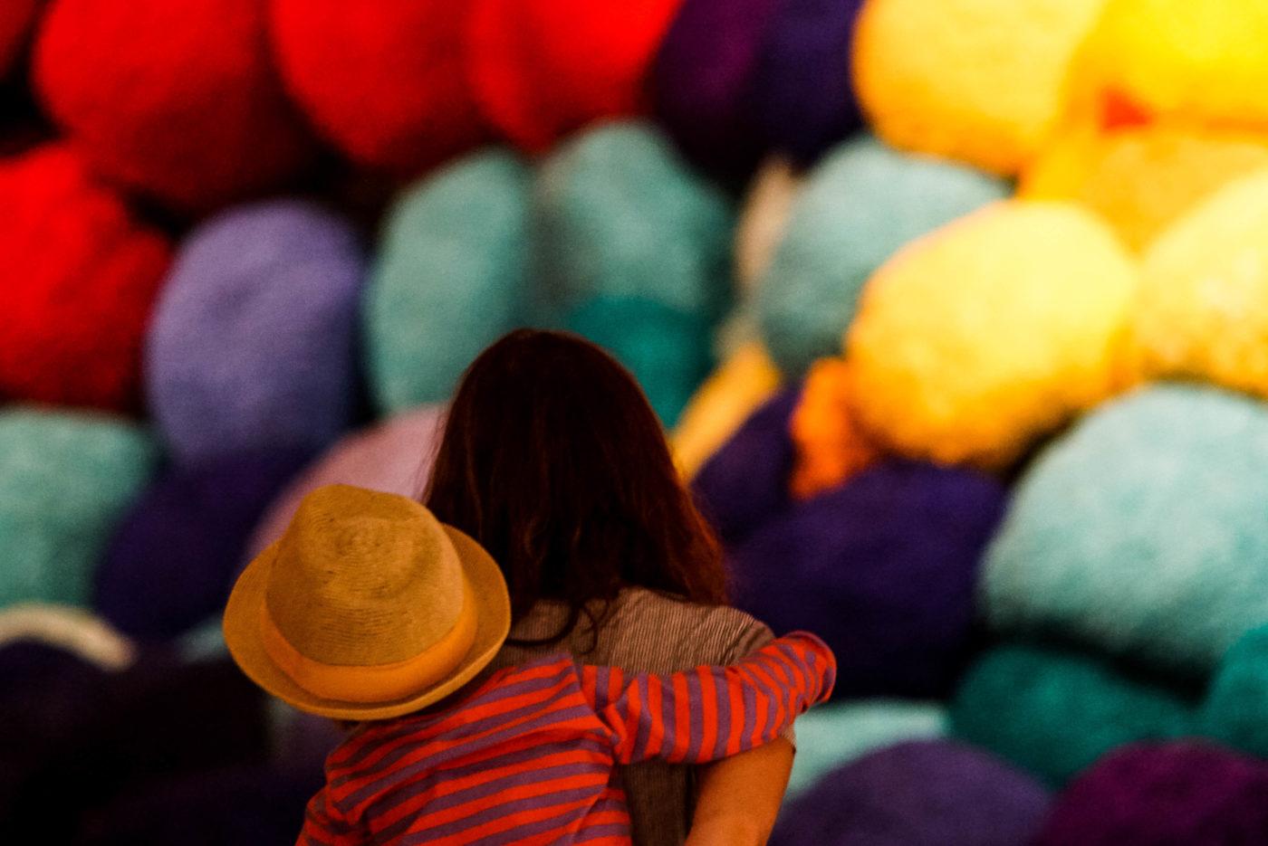 Im Vordergrund ist Lea zu sehen welche Luk auf dem Rücken trägt. Im Hintergrund sind große wollknäulartige Bälle in rot türkies gelb und lila