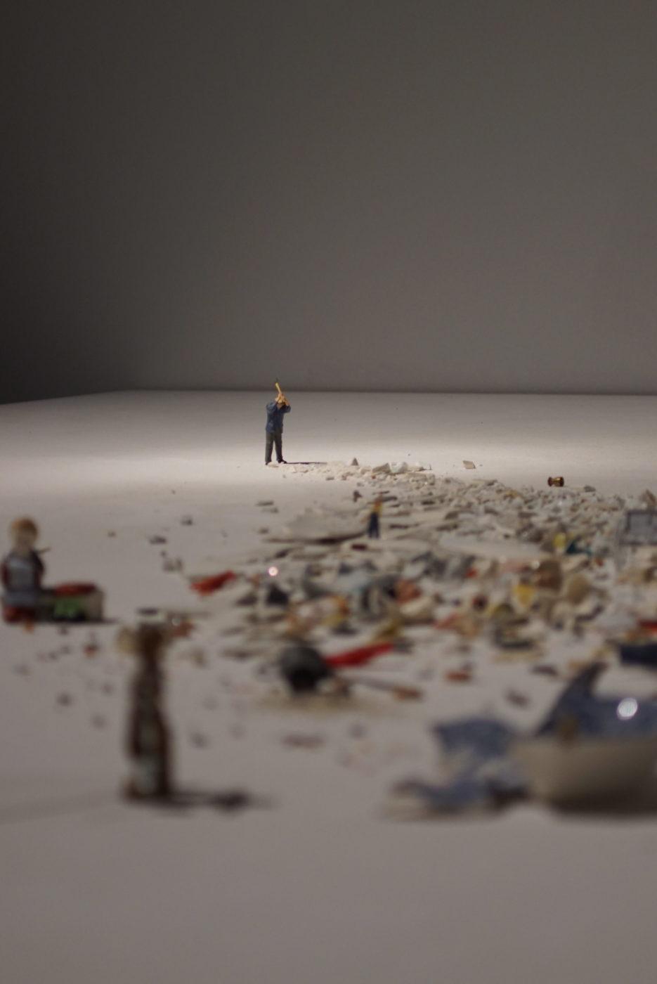 es sind mehrere Miniaturmenschen aus dem Modelleisenbahnbau zu sehen. Sie stehen vor Geröll und Schutt und einer dieser Menschen schlägt mit einem Vorschlaghammer auf den Schutt ein